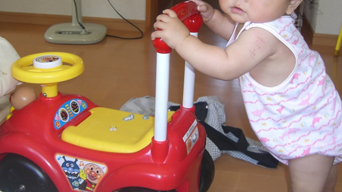おもちゃで歩く練習をするシャフリングベビー