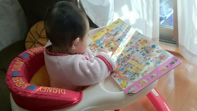 寝られないので自分で絵本を読む歩行器の中の赤ちゃん