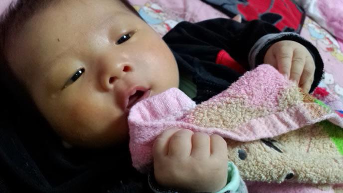 お気に入りの毛布を食べようとする赤ちゃん