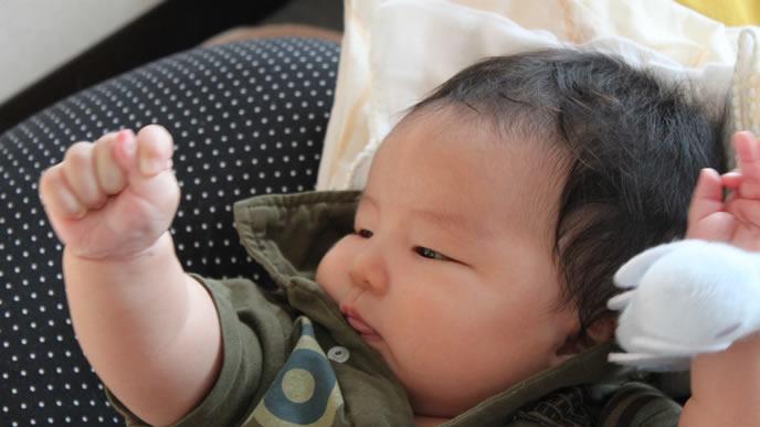 寝付けないので自分の手を見つめる赤ちゃん