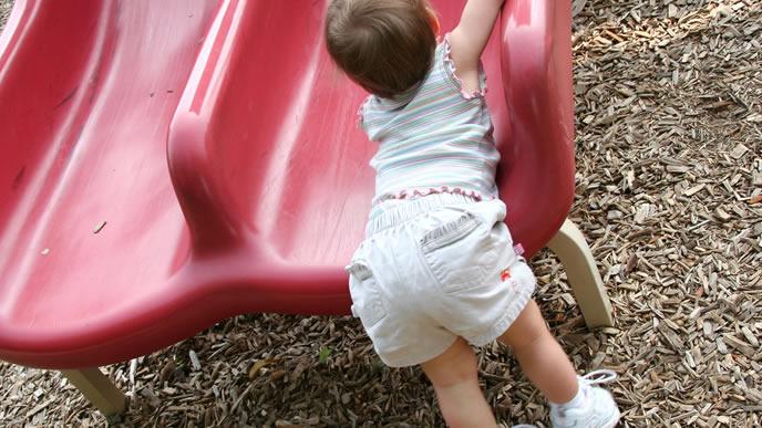 赤い滑り台で遊ぶ赤ちゃん