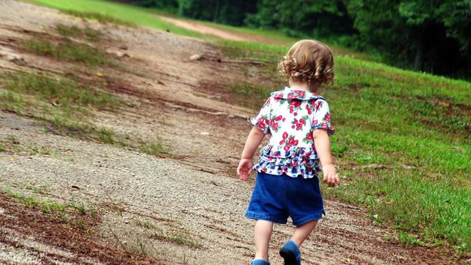 ママの先頭を歩き散歩をする赤ちゃん