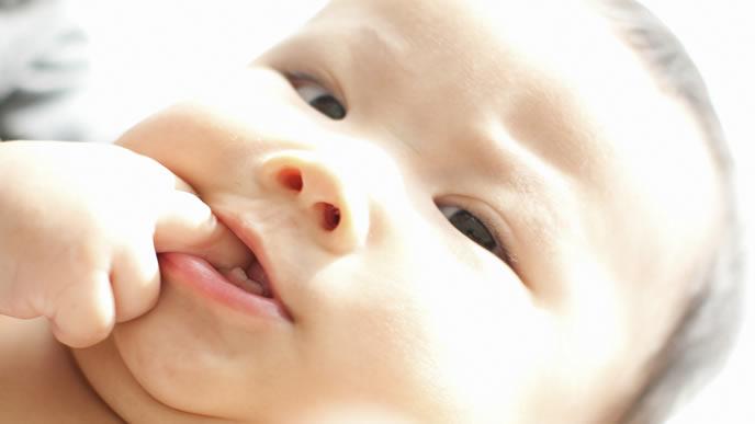 哺乳瓶の乳首の替わりに手をなめる赤ちゃん