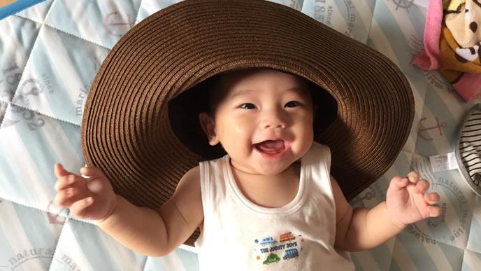 麦わら帽子にはしゃぐ赤ちゃん