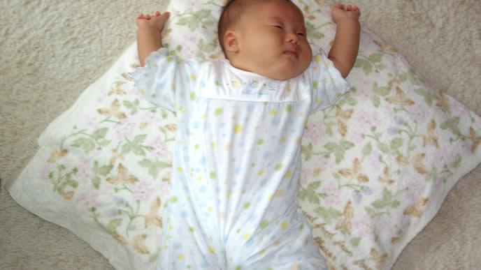 バンザイでお布団からはみ出て寝る赤ちゃん