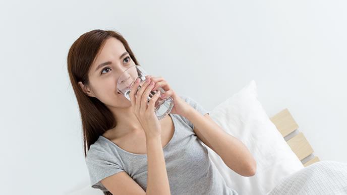安定期でリラックスして水を飲む妊婦