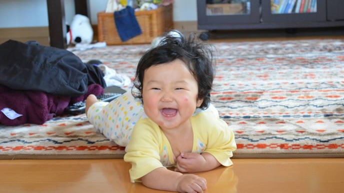 笑顔でずりばいする成長期の赤ちゃん