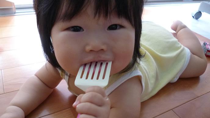 離乳食用のプラスチックの食器を口に入れる赤ちゃん