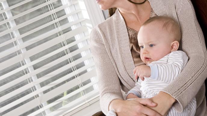 赤ちゃんの様子がおかしくママに抱っこされる赤ちゃん