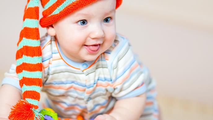 おすわりしながら笑顔でママを見る赤ちゃん