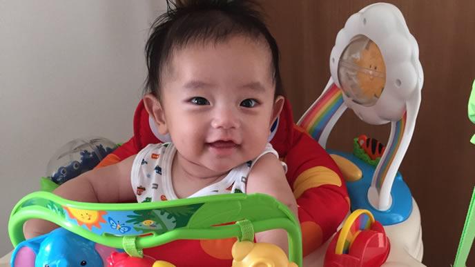 おもちゃで遊びながらテレビを見る赤ちゃん
