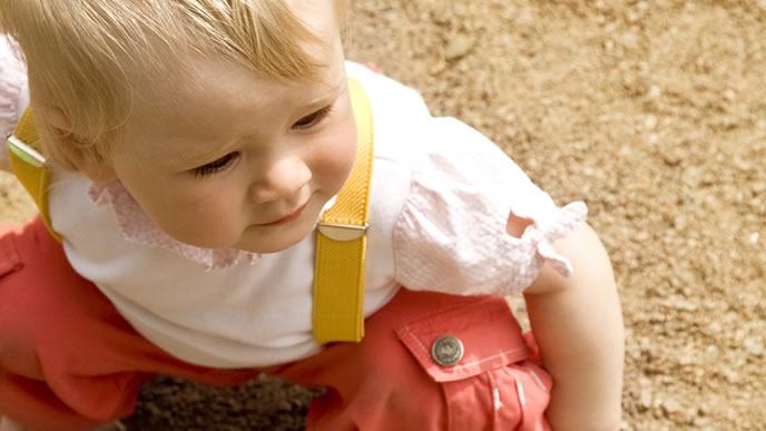 とびひの危険性がある砂場で遊ぶ赤ちゃん