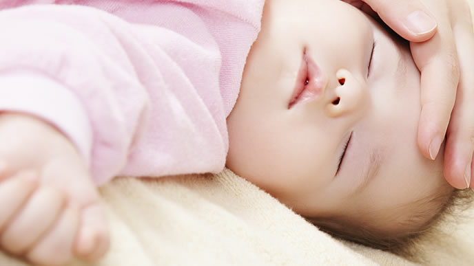 夜泣きした赤ちゃんを寝かしつけるママ