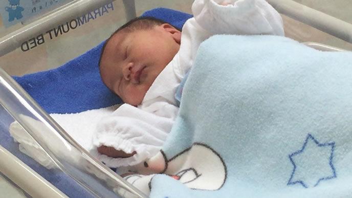 病院のベッドですやすや眠る赤ちゃん
