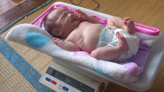 自宅の体重計に乗せられる赤ちゃん