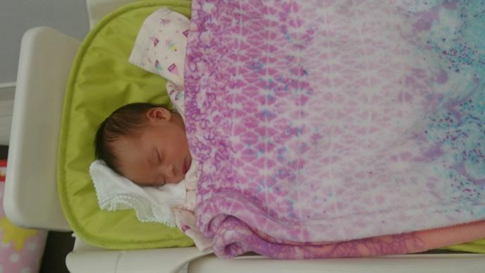 病院のベッドで眠る新生児の赤ちゃん