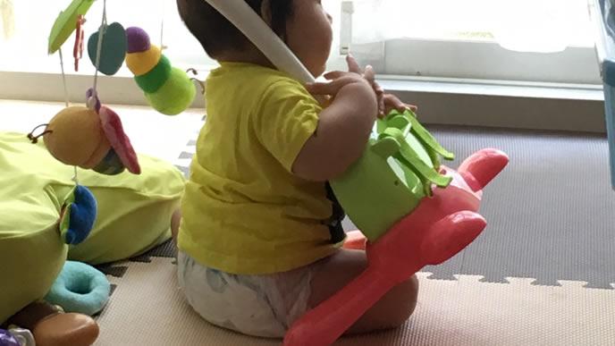 おもちゃを持ち上げる力持ちの赤ちゃん