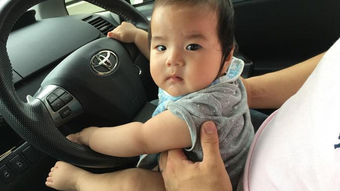 お座りして車のハンドルを握る赤ちゃん