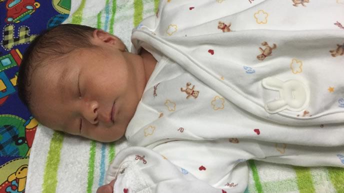 前開きの涼しい服装で寝る赤ちゃん