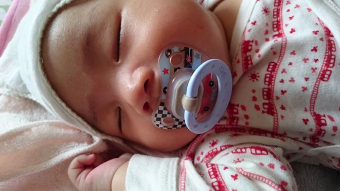 おしゃぶりをくわえながら寝る風邪をひいている赤ちゃん