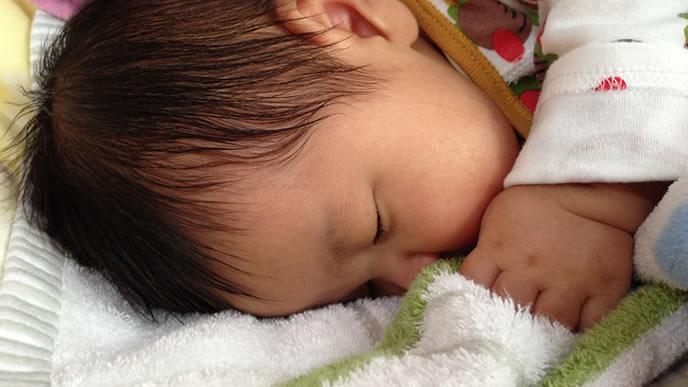 咳が止まらないので水分補給をする赤ちゃん