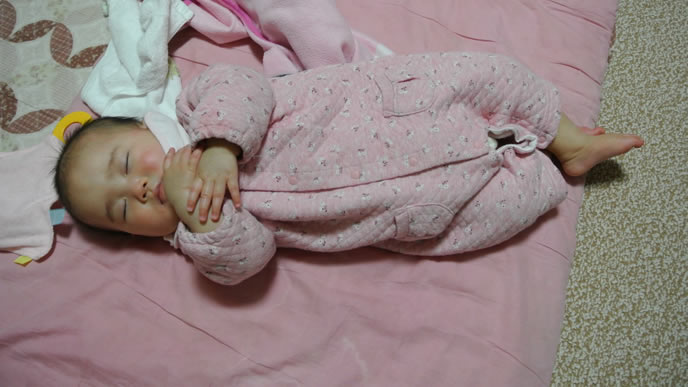 指をくわえて何かを祈るような寝相の赤ちゃん