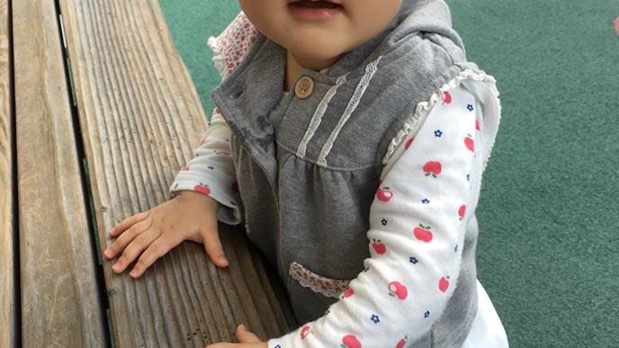 公園のベンチにつかまりたっちをする赤ちゃん