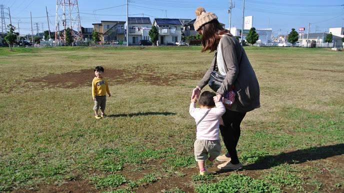 赤ちゃんのつかまり立ちの練習に付き合うママ