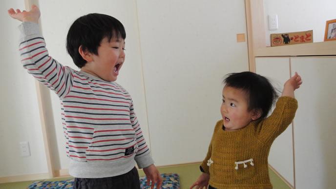 お兄ちゃんの真似をして手をあげる赤ちゃん