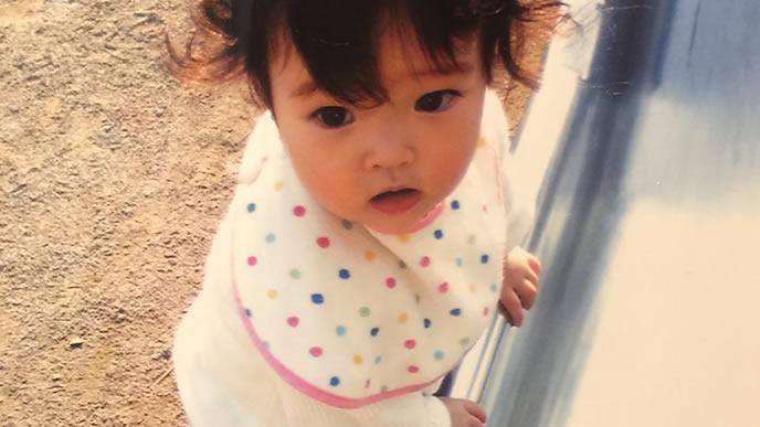 公園の滑り台でつかまり立ちを披露する赤ちゃん
