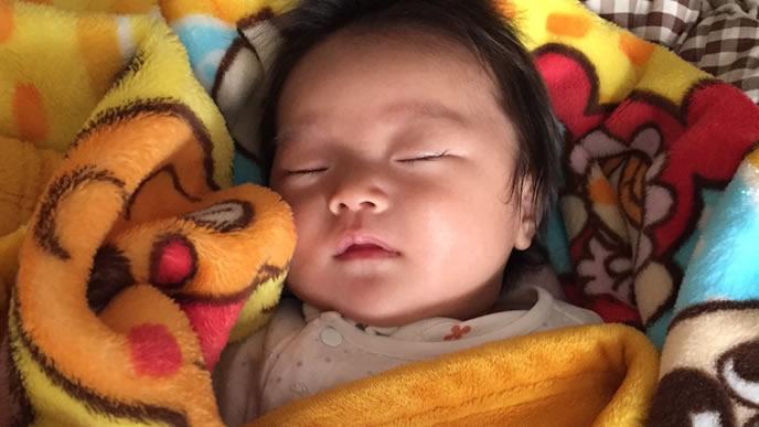 毛布に包まれて寝る赤ちゃん