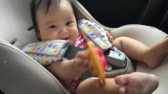 車に乗りながらラトルを振り回す元気な赤ちゃん