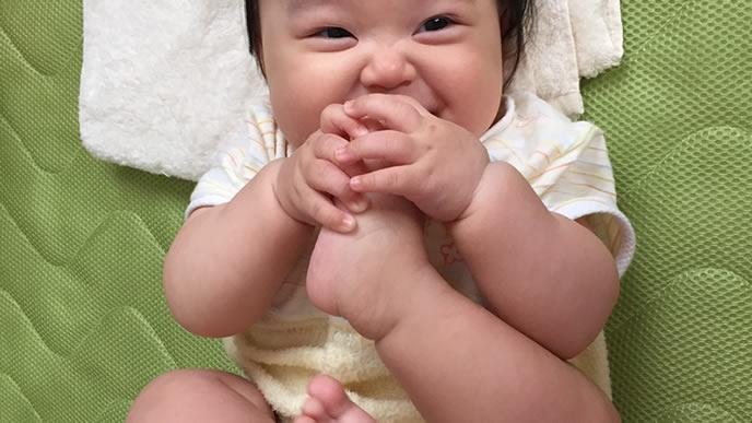 自分の足をなめてママを見つめる赤ちゃん