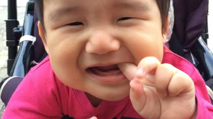 歯がむずがゆく指をくわえる赤ちゃん