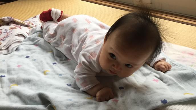 うつぶせ寝をしてママを見つめる赤ちゃん