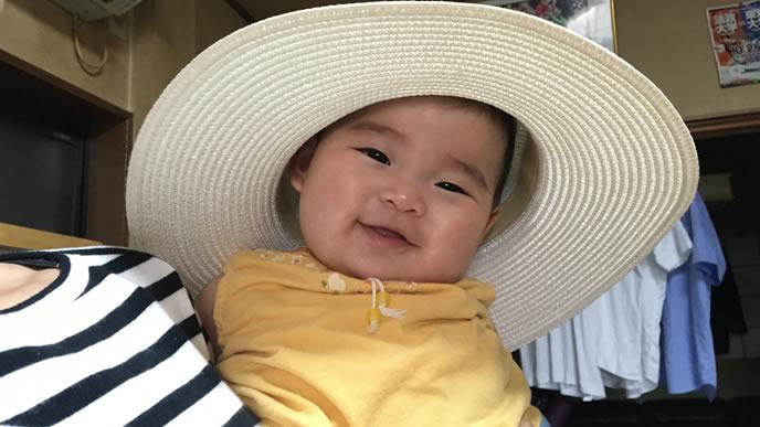 麦わら帽子をかぶって夏を満喫中の赤ちゃん