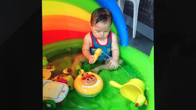 ビニールプールで水遊び中の赤ちゃん