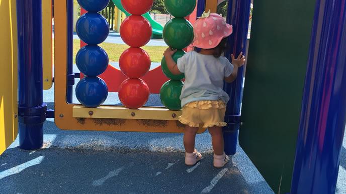 公園の遊具の隙間から除く赤ちゃん
