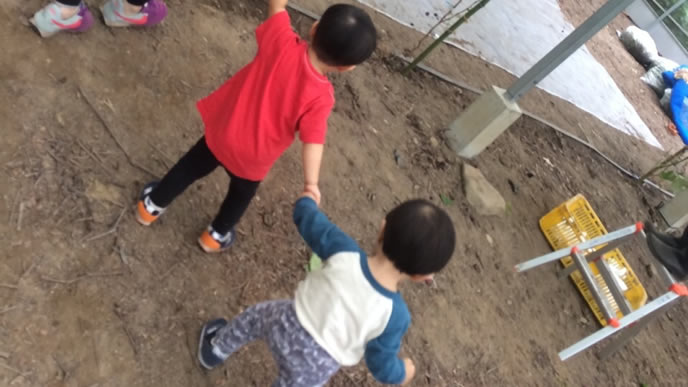 お兄ちゃんと手を繋ぎ公園を歩く赤ちゃん