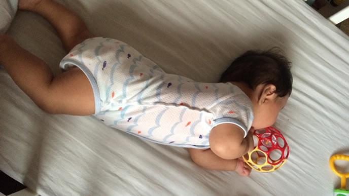 オーボールを口にくわえ寝返りしようとする赤ちゃん