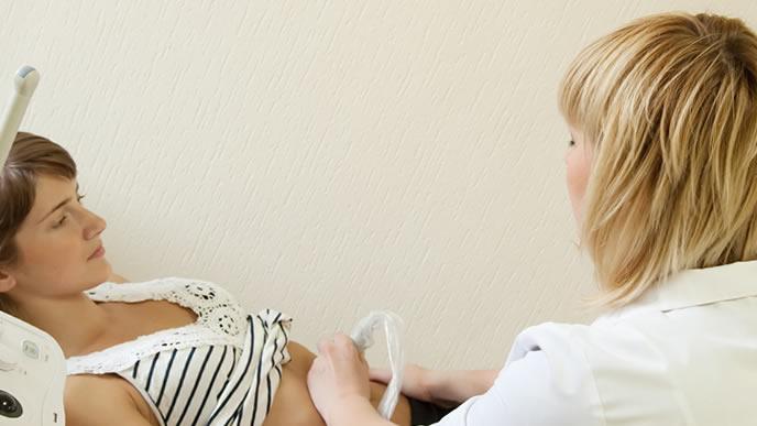 エコー検査で赤ちゃんの週数を調べる医師