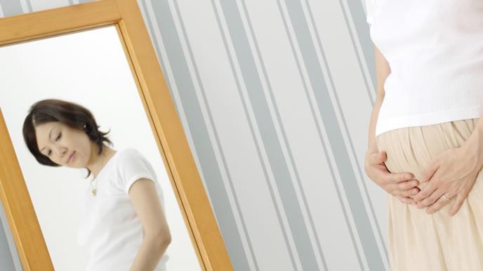 鏡で自分のお腹を確認する妊娠後期の女性