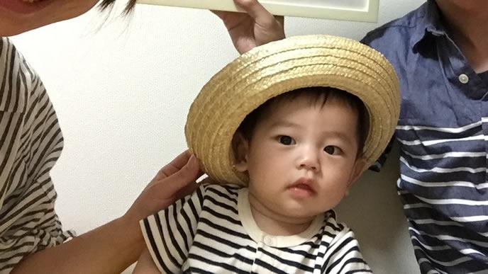 お気に入りの帽子をかぶって赤ちゃんと写真を取る家族