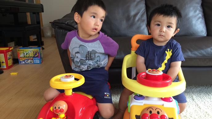 お気に入りのおもちゃに乗り記念写真をとる兄弟