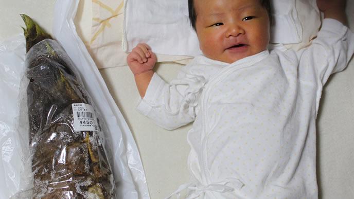 お祝いのタケノコと2ショットの赤ちゃん