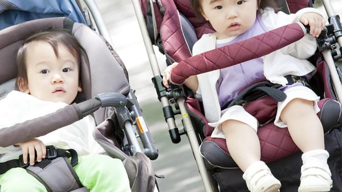 ベビーカーに乗る男の子と女の子の赤ちゃん