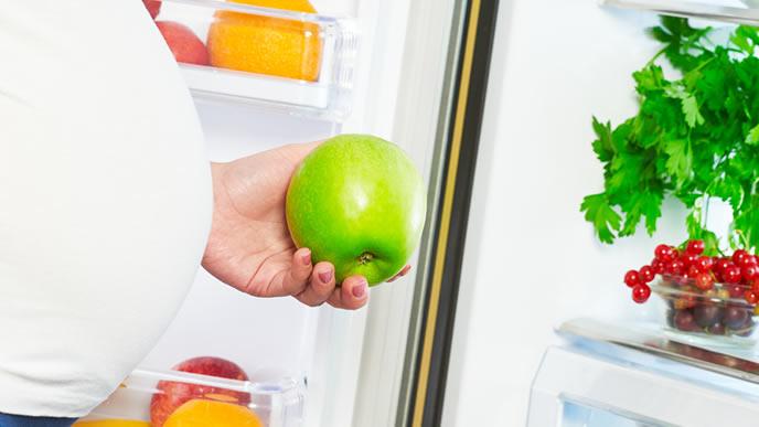 冷蔵庫のリンゴを手にして食べるか悩む妊婦