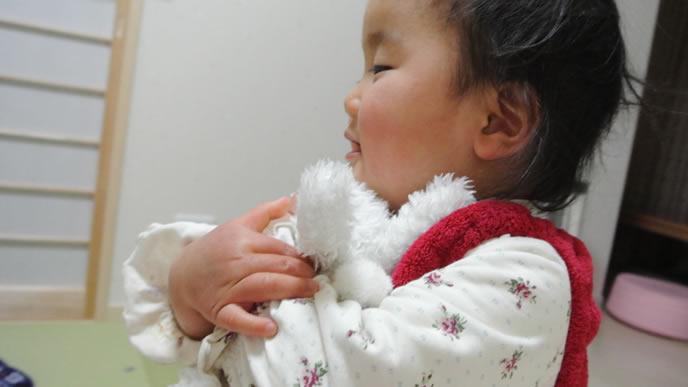 ぬいぐるみを大事そうに抱える赤ちゃん