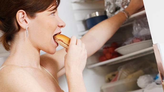 お腹が減り冷蔵庫のパンを間食する妊婦