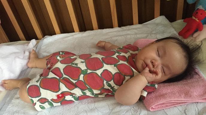 ベビーベッドで指をしゃぶって寝ている赤ちゃん